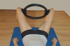 esercizio per il bacino  con un cerchio di pilates tra le gambe