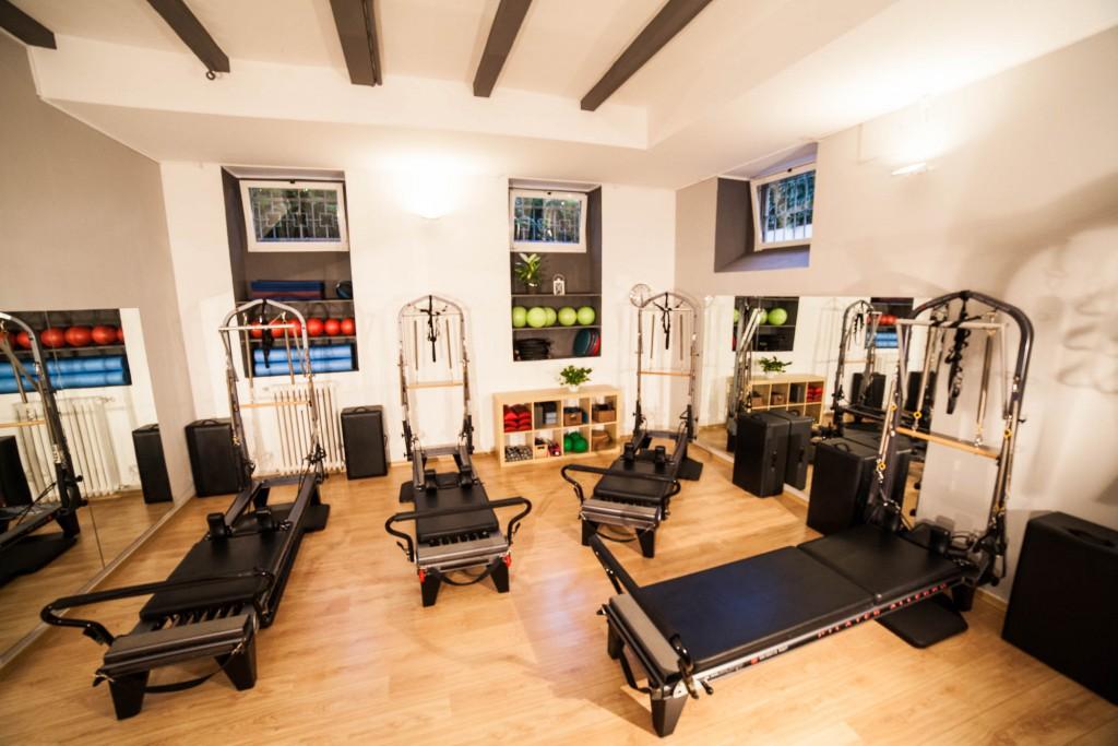 una grande sala composta da lettini di Pilates chiamati Reformer